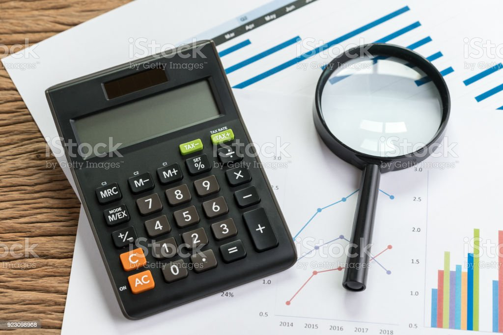 Business perfomance review or KPI key point indicator estimation concept, calculator with magnifier glass on pile of graph and chart performance print paper on wood table stock photo