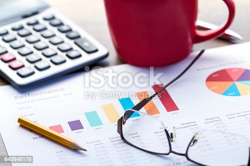 Business performance analysis with colorful bar graph, calculator and red coffee cup