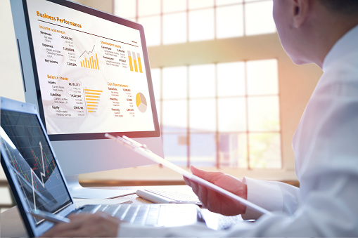 Businessman analysing on business performance on desktop and notebook computer with orange-gold graphs.