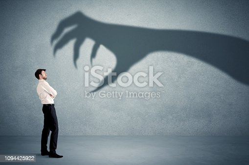 istock Business person afraid of a big monster claw shadow concept 1094425922