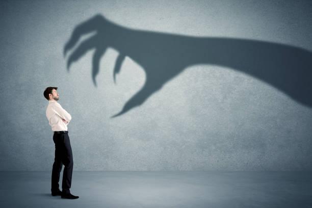 persona de negocios de un concepto de gran monstruo garra sombra - monstruo fotografías e imágenes de stock