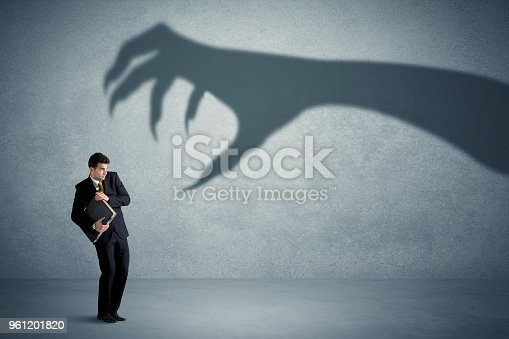 istock Business person afraid of a big monster claw shadow concept 961201820