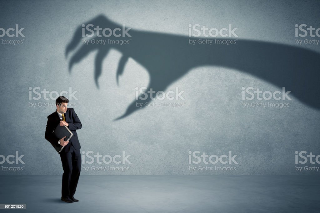 Business person afraid of a big monster claw shadow concept stock photo