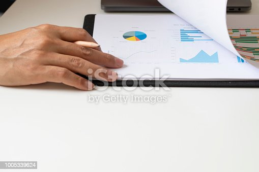 1068812018istockphoto Business person analyzing financial on paperwork 1005339624