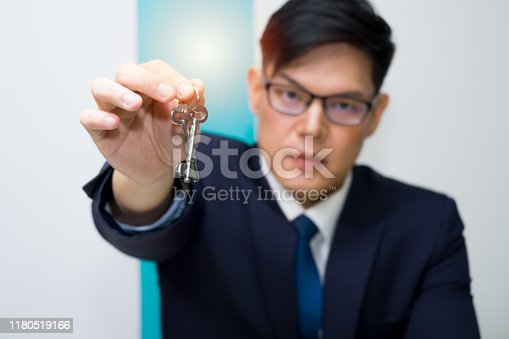 A business person car rental operator or lodging wearing blue suit and glasses is gesture hand over the room key with depth of field and blurred effect.