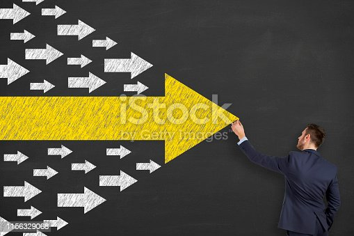 istock Business Person Drawing Leadership Concepts with Arrows on Chalkboard Background 1156329068
