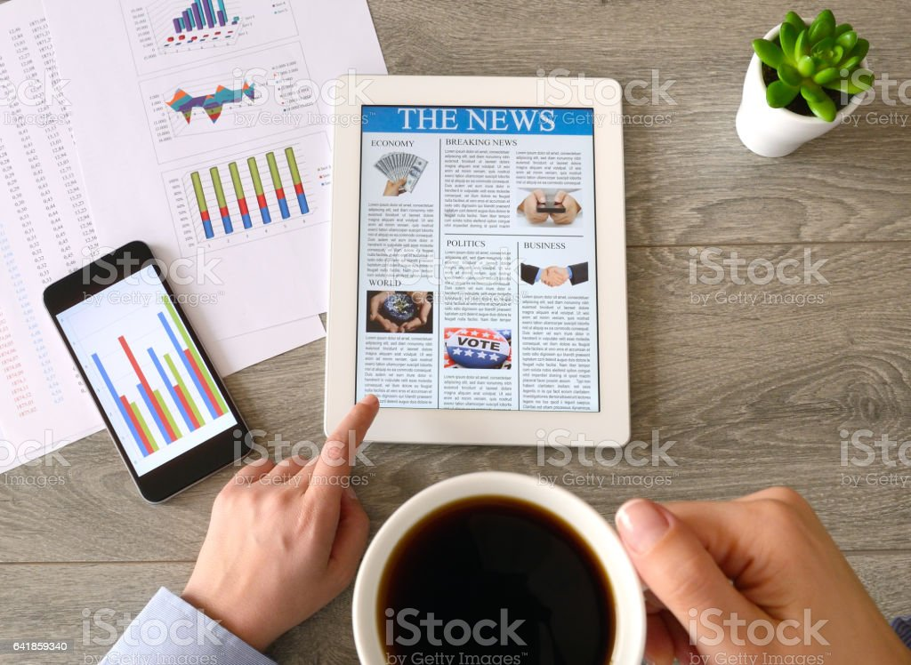 Business person drinking coffee and reading news on tablet pc stock photo
