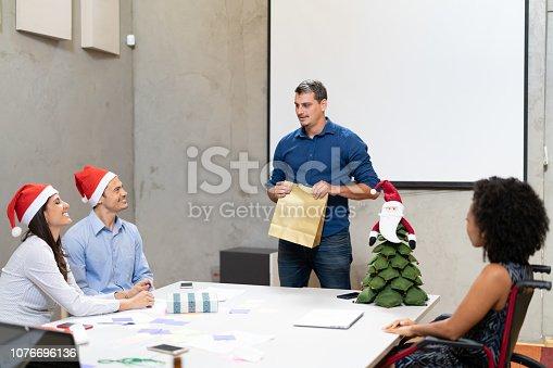 istock Business person Exchanging Christmas presents at work / Amigo Secreto 1076696136
