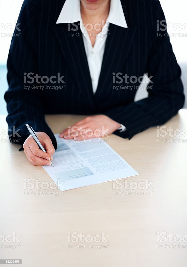 Business person filling a document at the table royalty-free stock photo