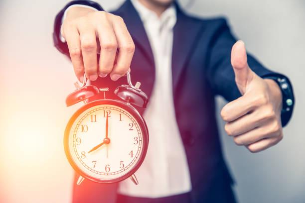 良い時間や時間のコンセプトで適切な時間の仕事のための時計で親指を示すビジネスパーソンの手。 - 出勤 ストックフォトと画像