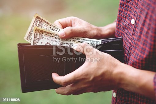 istock Business Person holding an wallet in the hands of an man no money have a little money. Poverty poor Bankruptcy in concept. 951149808