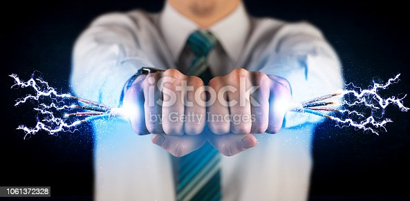 istock Business person holding electrical powered wires 1061372328