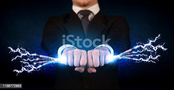 istock Business person holding electrical powered wires 1158772953
