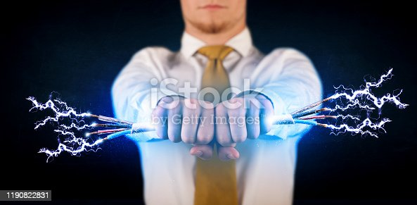 1152920014 istock photo Business person holding electrical powered wires 1190822831