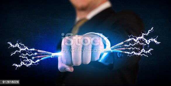 istock Business person holding electrical powered wires 912618026