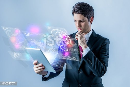 810397364 istock photo business person holding futuristic tablet PC 810397074