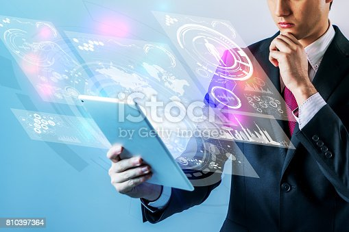 istock business person holding futuristic tablet PC 810397364