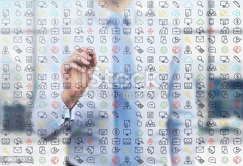 A business person is writing a numerous business and social media icons on the glass screen in the modern panoramic office.