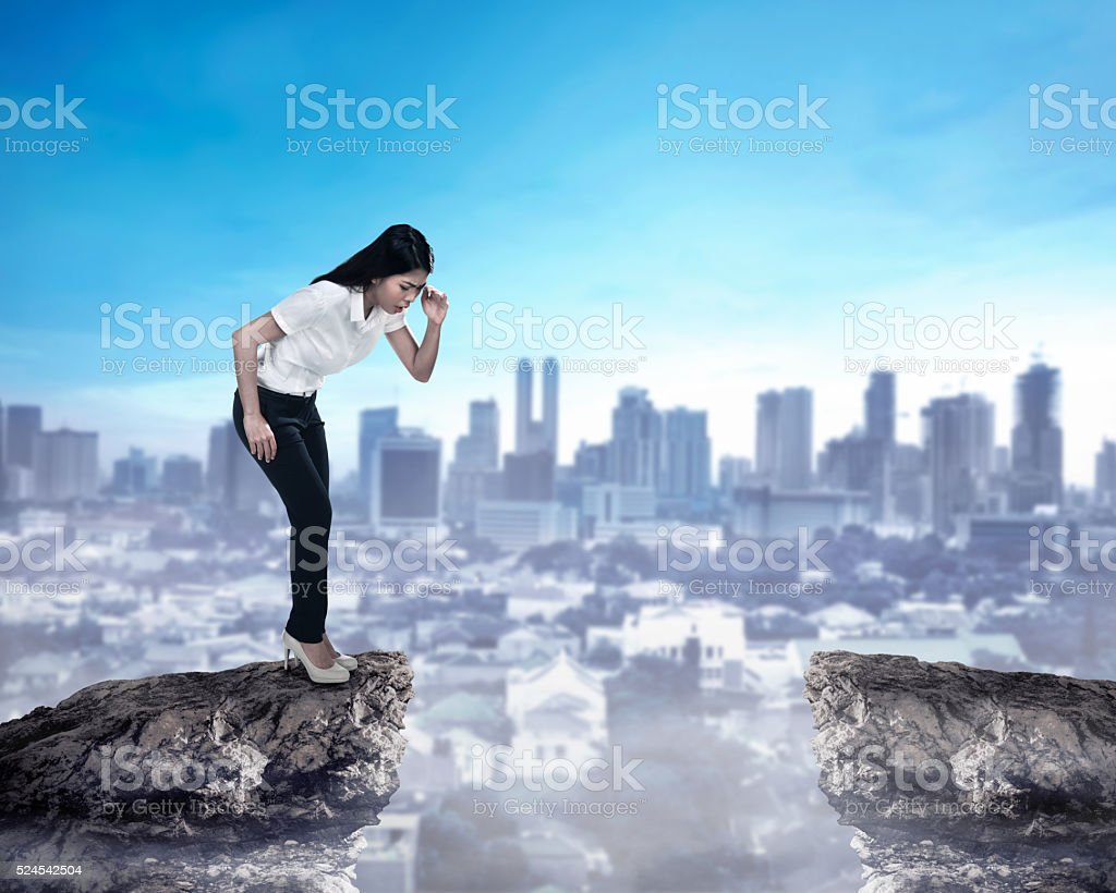 Business person looking down from top of the cliff stock photo