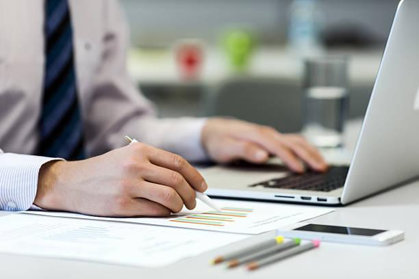 geschäftsmann liest daten auf papier diagramme und computer - lesen arbeitsblätter stock-fotos und bilder
