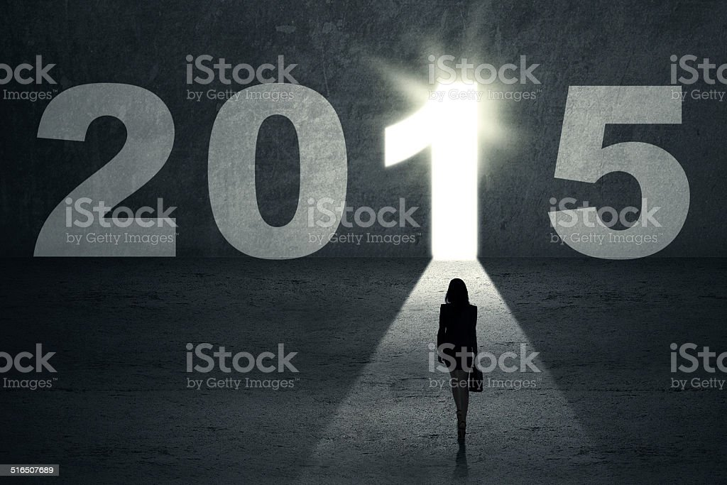 Woman carrying briefcase stepping toward bright door to future 2015