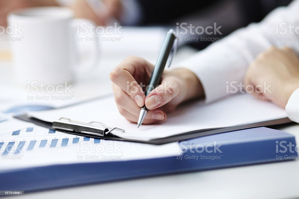 Business person taking notes with coffee Close-up of female hand making notes Ballpoint Pen Stock Photo