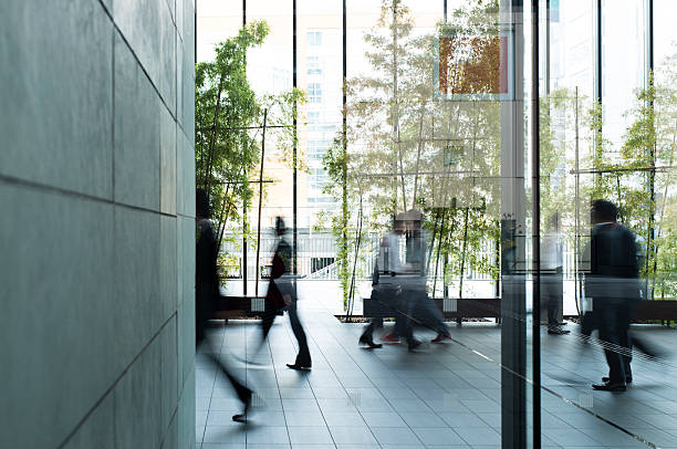 business person walking in a urban building - green color stock pictures, royalty-free photos & images