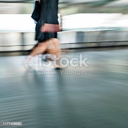 171150458 istock photo Business person walking on city footbridge 1177408880