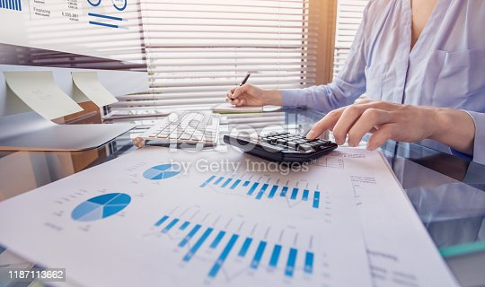 Business person working on financial report and analyzing revenue and expenses data with calculator in office
