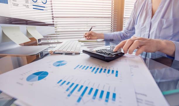 Geschäftsmann, der an Finanzberichten arbeitet und Umsatz- und Spesendaten mit rechnerimt analysiert – Foto