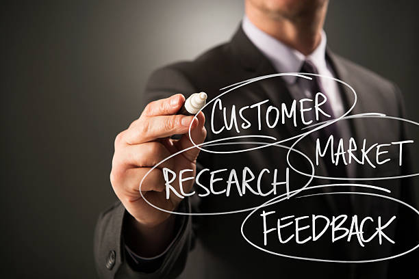 business person writing market research customer feedback on screen - market research stock photos and pictures
