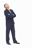 Full length of a happy business man with arms crossed standing against white background