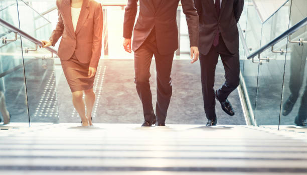 business persons going up the stairs. - staircase stock photos and pictures