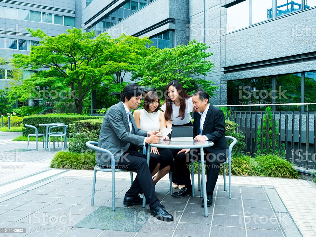 Business Persons Having a Meeting Outdoors stock photo