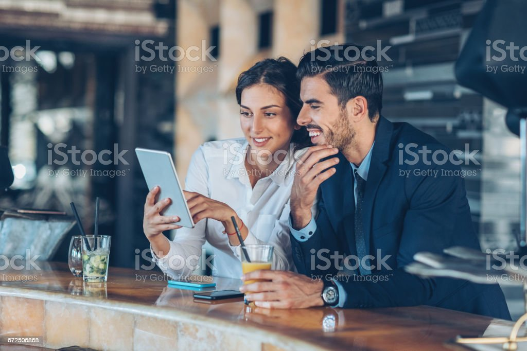 Business persons with digital tablet and drinks in hotel's lobby stock photo