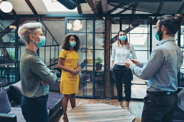 Business persons with protective masks meet in a co-working area stock photo