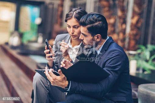 istock Business persons with smart phone and documents 673323632