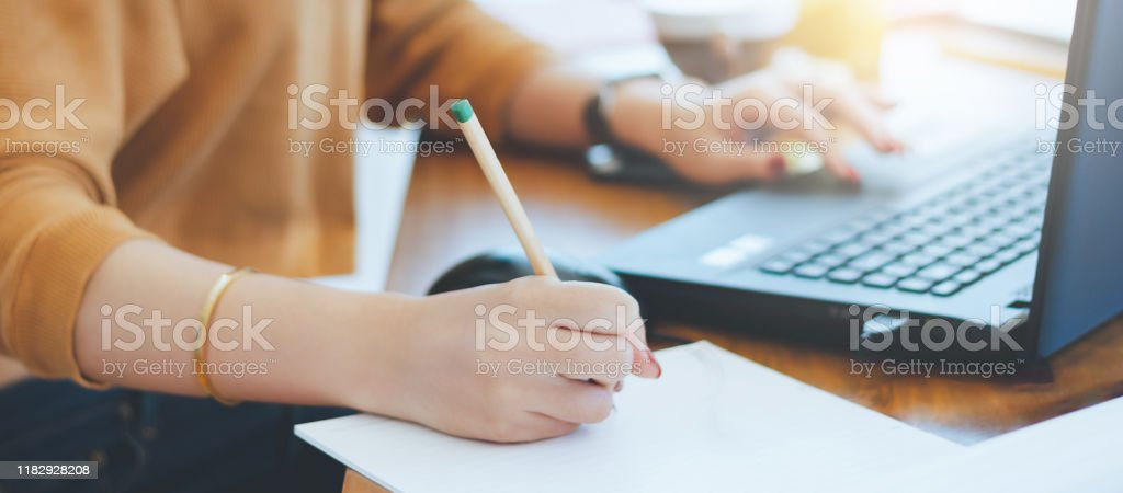 business Closeup of hand asian businesswoman writing on paper and using laptop to searching data for working Adult Stock Photo