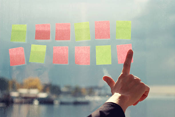 Business planning. Stickers on the window, the hand holding stickers stock photo