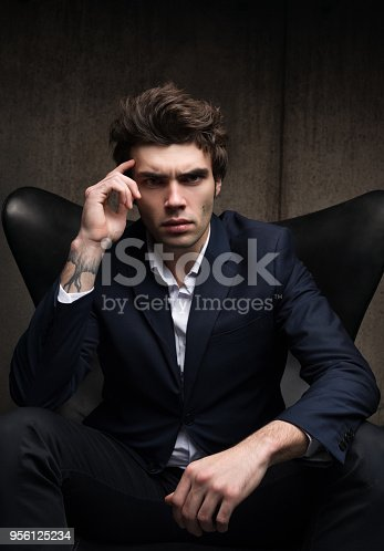 istock Business portrait of a serious young man sitting in a chair 956125234