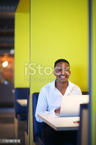 istock Business Portrait of young African male sitting in a yellow office cubicle 1131967918