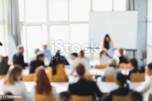 Defocused image of people attending a lecture