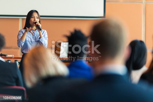 An Asian female presenter interacting with the audience at a business presentation in the board room