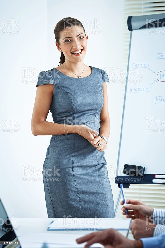 Business presentation Focus on the happy businesswoman standing next to the flipchart and giving presentation to his business colleagues. Achievement Stock Photo