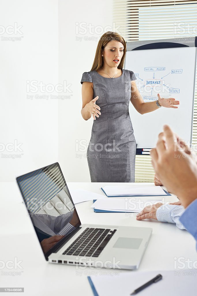 Business presentation Businesswoman standing in front of flipchart and giving presentation to his business colleague. Achievement Stock Photo