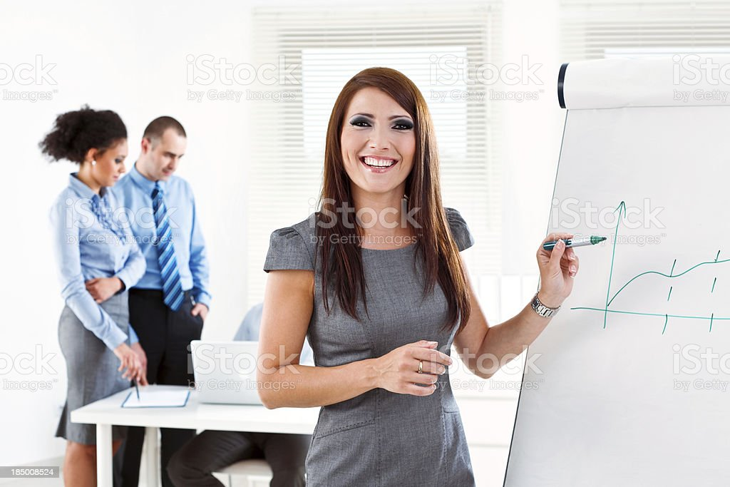 Business presentation Focus on the young businesswoman giving presentation on the flip chart and smiling at camera with her colleagues working in the background. Adult Stock Photo