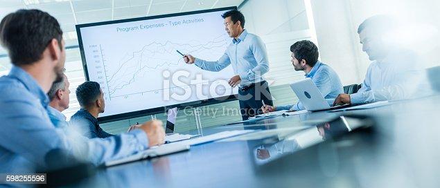 Businessman giving presentation in conference room.