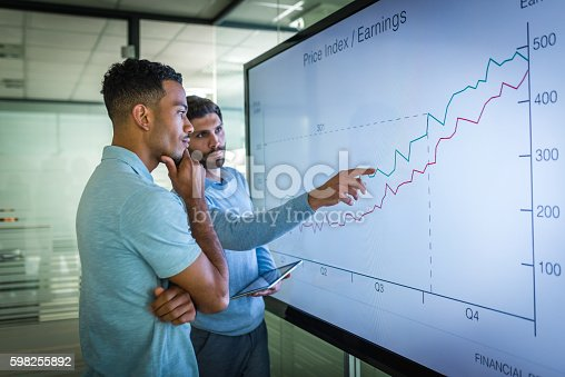 Businessman explaining line graph to his coworker.