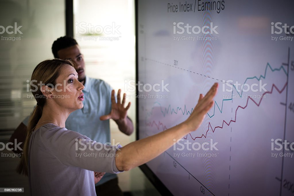 Business presentation Businesswoman explaining graph to his coworker in conference room. 30-39 Years Stock Photo
