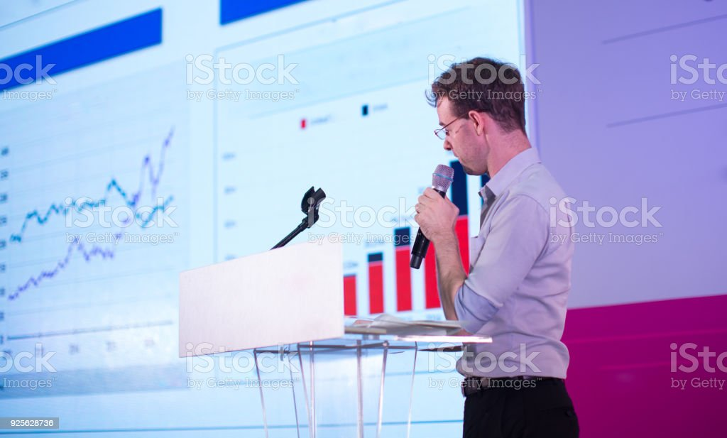 Business Presentation. Presenter Showing Charts and Graphs. stock photo